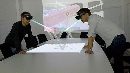 2 Männer mit AR-Brille lehnen über einem Konstruktionstisch