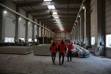 Die Exkursionsteilnehmer stehen in der Produktionshalle.
