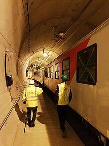 zwei Männer gehen in einem Eisenbahntunnel an einem stehenden Waggon vorbei