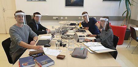 Vier Assistent*innen sitzen an einem Tisch, jede hat ein Notebook und Unterlagen dabei. Alle haben Schutzmasken auf.