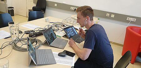 Ein Assistent sitzt an einem Tisch mit drei Notebooks vor sich und vielen Kabeln rund herum.