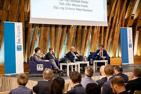 Podiumsdiskussion mit vier Teilnehmern.