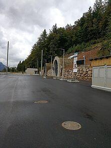 ein asphaltierter Platz mit einer Baracke am Rand; vom Platz führt eine Tunneleinfahrt in den Erzberg; im Hintergrund ein Nadelwald